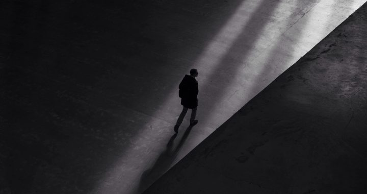 Image of a man in dark surroundings walking toward a shadowy light source.