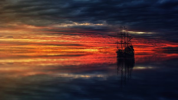 Image of an old sailing ship at sea waiting for the light to break through a heavily clouded sunrise.