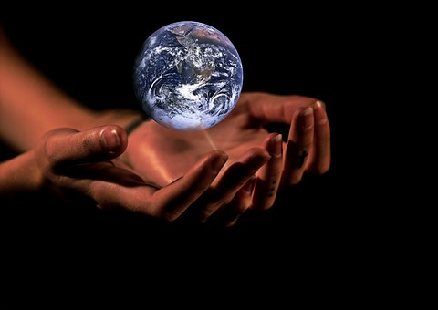 Image of a woman's hands with planet earth hovering above them.